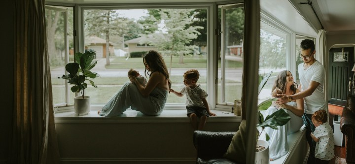 family sitting by the window with their little new baby girl