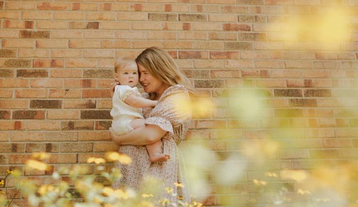 mom holding baby near brick wALL