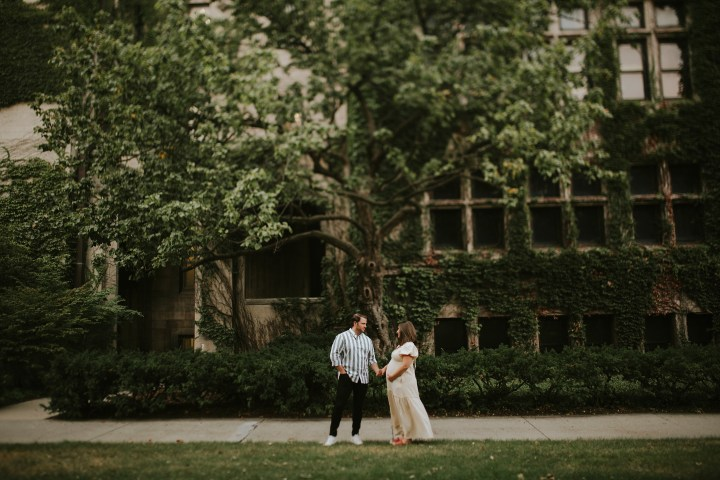 epectant couple in front of a tree