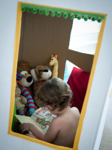 little boy reading books in a reading cubby house