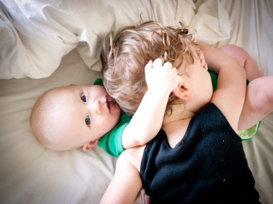 toddler and baby wrestling