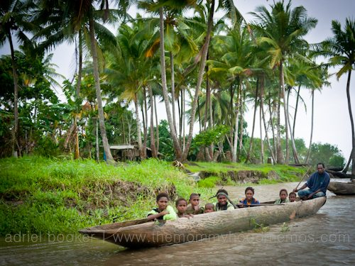 Family in canoe. Giving birth in the Bamu River region, Western Province, PNG.