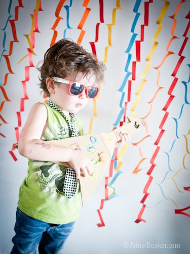 Rockstar Kids Birthday Party photo booth with paper strips and a couple of easy props.
