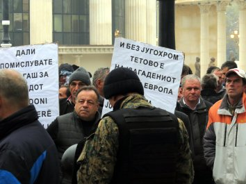 "Police officers stands in front of the worker with the placards ""And without Jugohrom, Tetovo is most polluted city in Europe."""