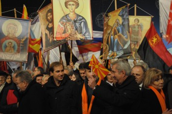 Ljupco Dimovski of Socialist Party holds the flag of Republic of Macedonia during the rally in which Orthodox placards with saints appeared as part of the rally iconography.
