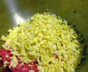 Shredded Napa cabbage in bowl with other ingredients