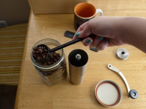 Scooping coffee beans into a JavaPresse coffee grinder, which is open, the crank on the table next to the mason jar lid, a mug in the background.