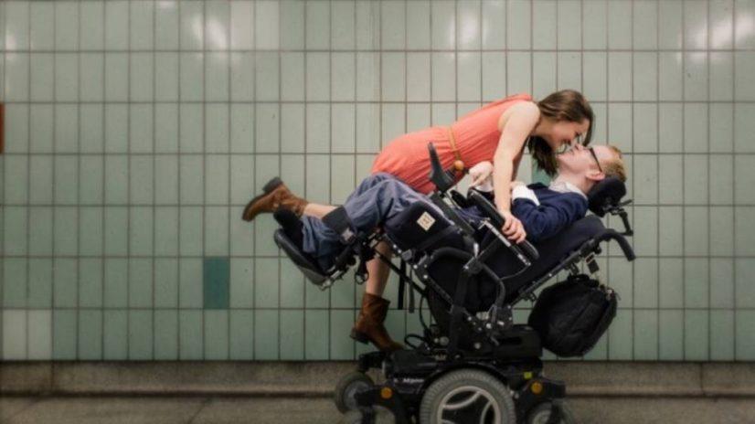 Woman Kissing Boyfriend in Wheelchair