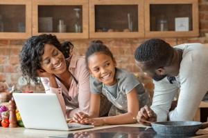Family using laptop at kitchen counter, radical healing.