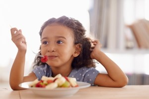 Image of a cute little girl eating fruit salad at a table showing healthy eating under new dietary guidelines.