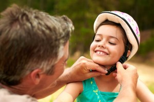 Father fastening bicycle helmet on daughter.