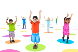 Children having fun on multi-colored flooring with dots.