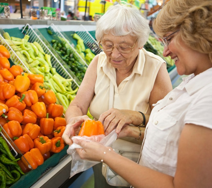 Two women shopping in the produce section.