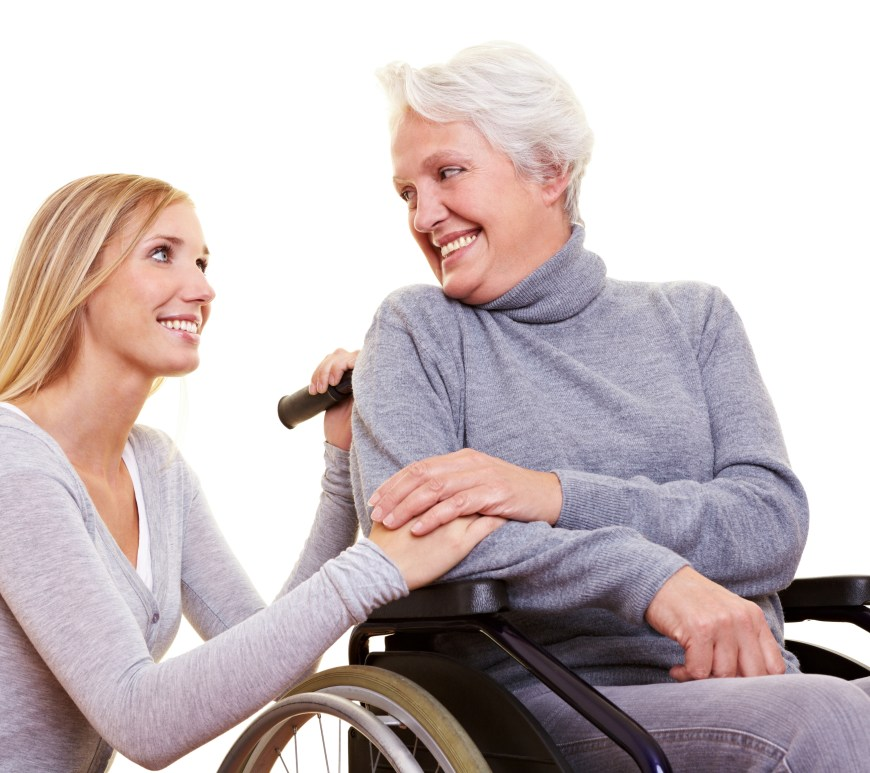 Senior woman in wheelchair with younger woman crouching next to her and smiling.