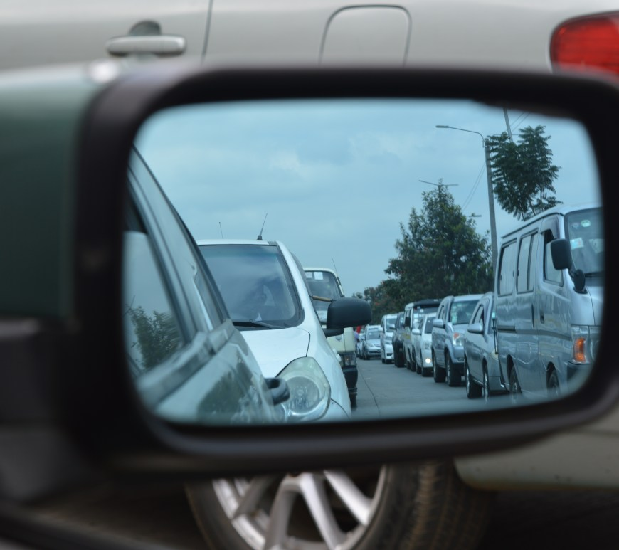 Side view mirror with traffic reflected in it.