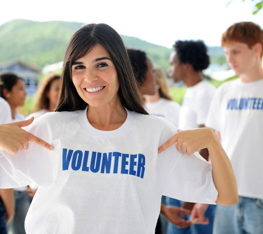 "Woman wearing a white shirt that says ""Volunteer""."