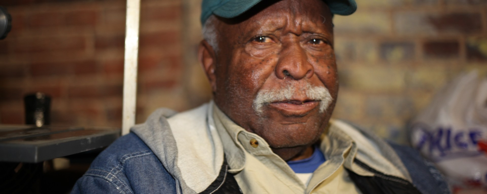 Black man wearing a jean jacket and baseball cap.