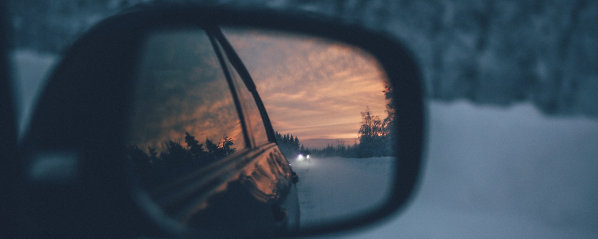 Car mirror reflecting a sunset.