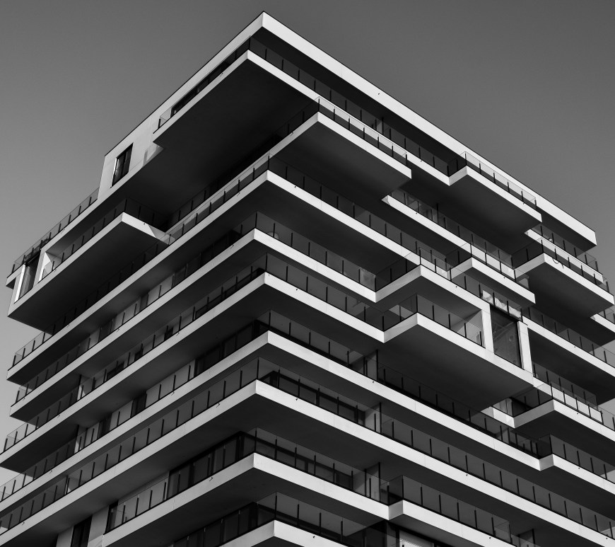 Black and white photo of a multi-story apartment building.