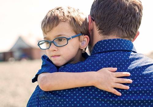 A boy looks over his father's shoulder as his father carries him.