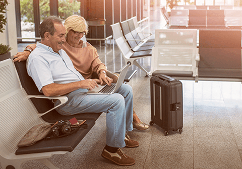 A couple sit on a bench in an airport while using a laptop.