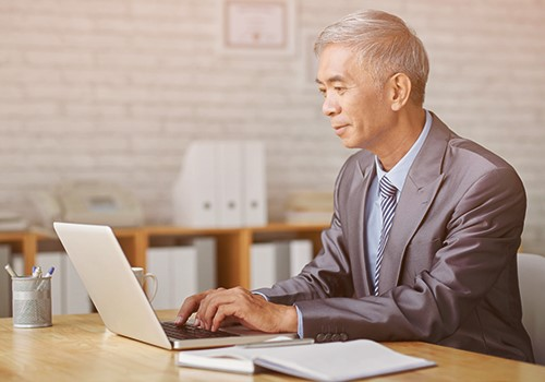 A man wearing a suit uses a laptop while sitting at a desk.