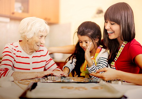 Three generations of women making cookies together.