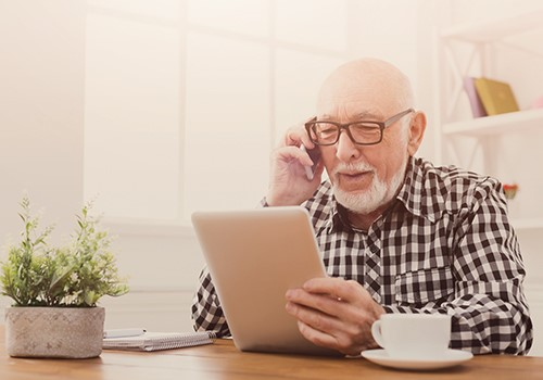A man with gray hair talks on the phone while looking at his tablet.