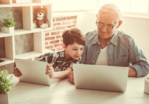 An older man and young boy use laptops while sitting together.