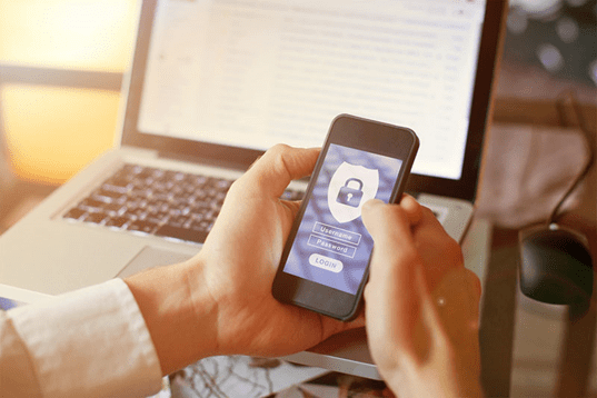 A man holding a cell phone showing a login screen asking for username and password.