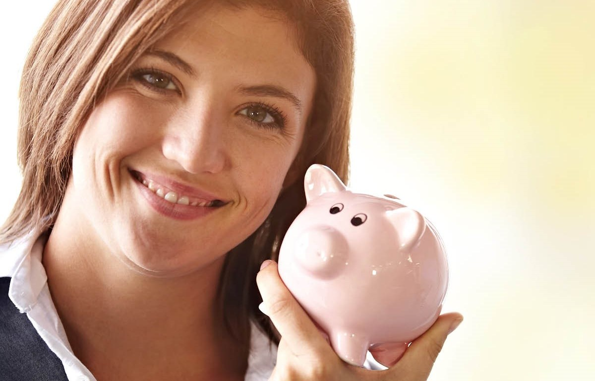 A woman smiles while holding a small pig-shaped piggy bank.
