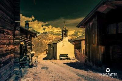 Infraroodfoto van een Oud Wit Kerkje in Zwitserland, in de bergen tegen een donkere wolkenlucht. Met de Bietschhorn op de achtergrond.