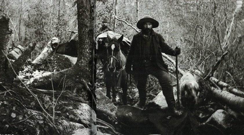 jack london standing with a donkey laden with supplies for the long trip in the yukon