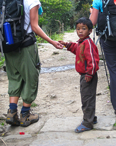Kid handing out flowers to the trekkers in Nepal