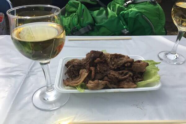 屋台料理の焼肉とワインの写真