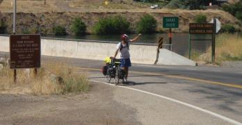 Brian pushes a busted bicycle across the Idaho border.