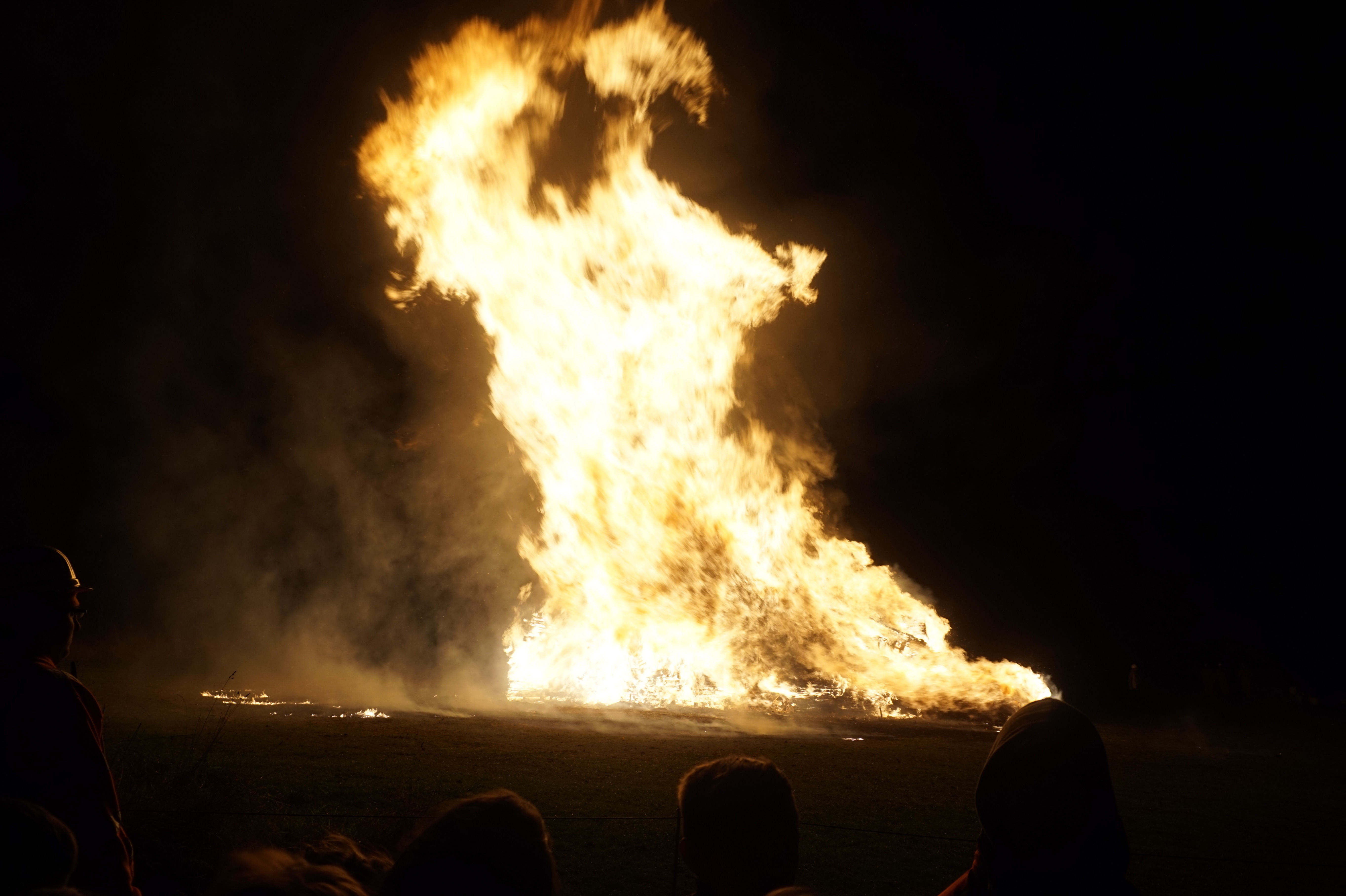 A giant bonfire rages into the sky at night.