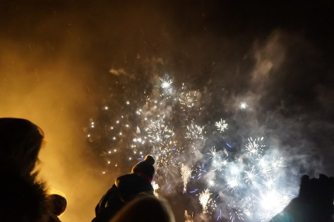 White fireworks explode in the night sky while onlookers watch from beneath.