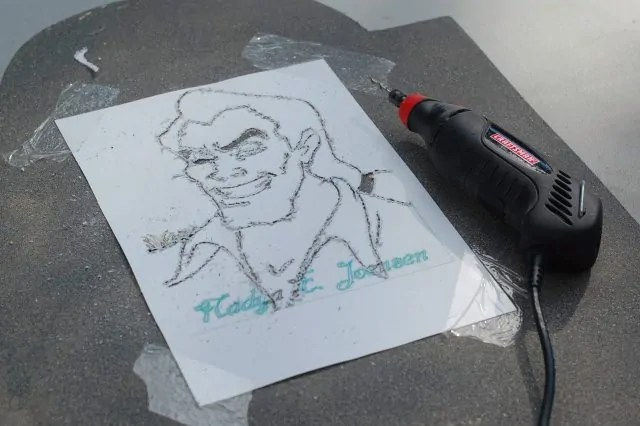 Outline of Gaston on paper taped to wooden tombstone and dremel laying next to it after etching the picture.
