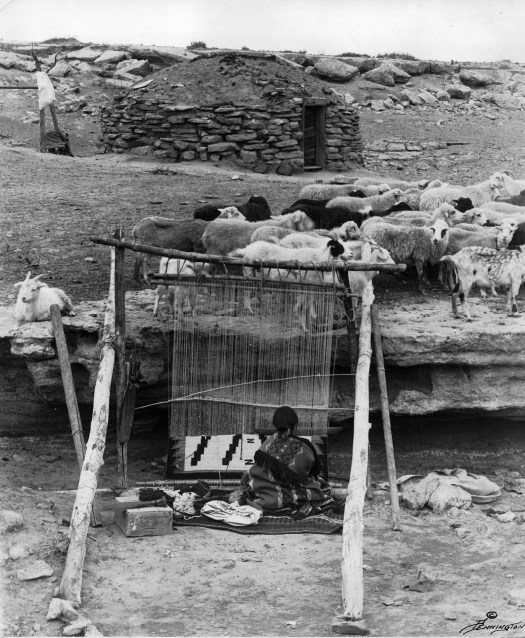 The proceeds from weaving wool into blankets was the only source of income for Navajo women. Here we see a weaving setup, a flock of sheep and a hogan.
