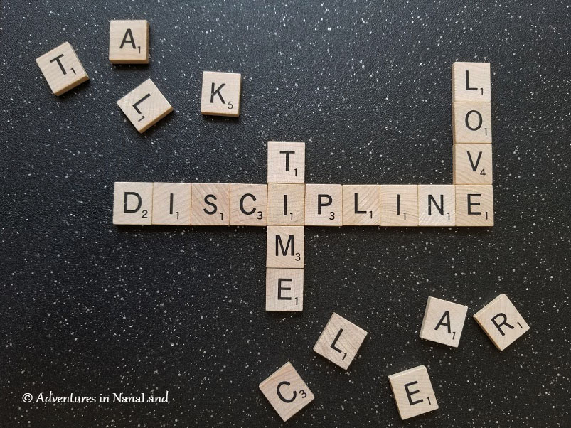 The words discipline love and time spelled out with scrabble tiles