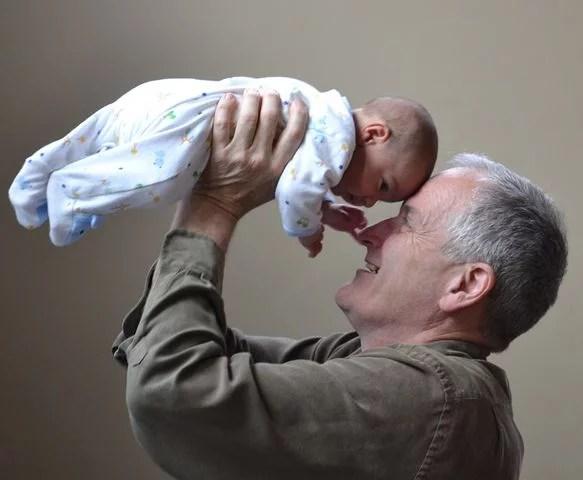 Grandfather holding new grandchild, grandparents