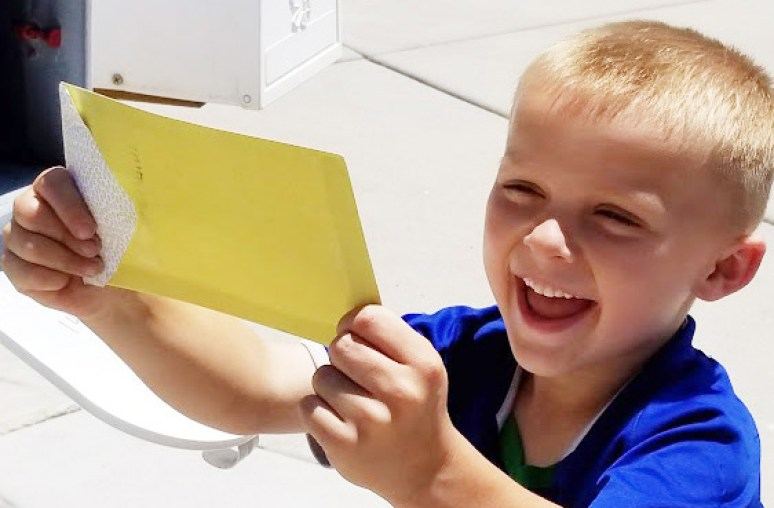 Happy child getting a letter from a mailbox
