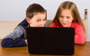 Young girl and boy excitedly looking at laptop computer - Adventures in NanaLand