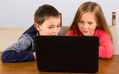 Young girl and boy excitedly looking at laptop computer