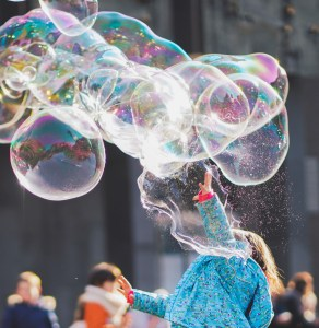 Girl playing with lots of very large bubbles - Adventures in NanaLand - Things to do with grandkids