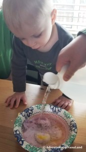 Baby watching vinegar being poured over baking soda rocks - Magic Rainbow Rocks - Adventures in NanaLand