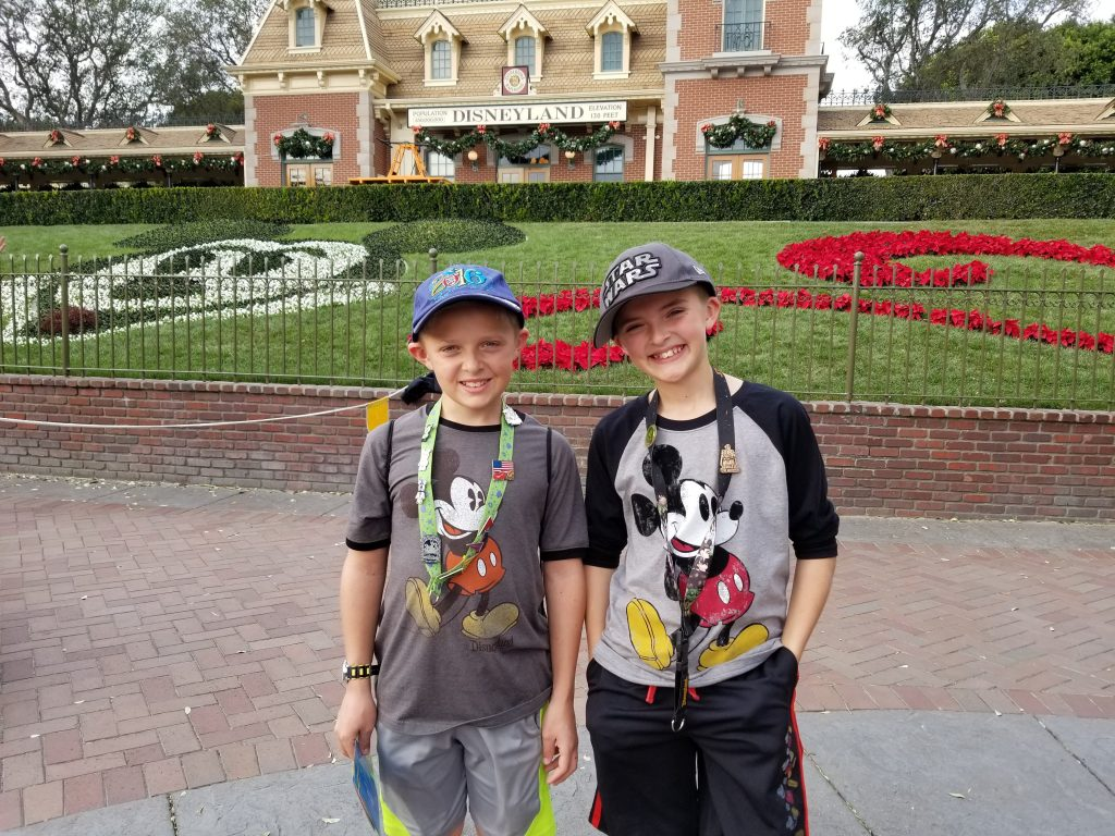 Boys stnding inside the Disneyland Maingate area - Beating the Disneyland Crowds - Adventures in NanaLand