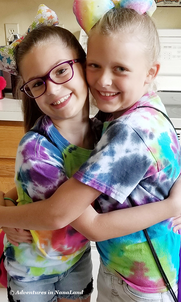 Two girls hugging each other wearing tie dye shirts - Grandma Camp Memories - Adventures in NanaLand