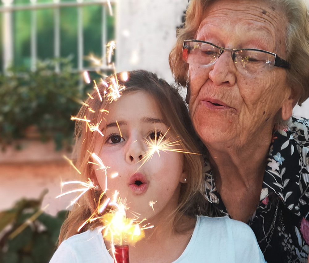 Grandmother and granddaughter blowing out candles that look like fireworks - Grandparents Day activities - Adventures in NanaLand